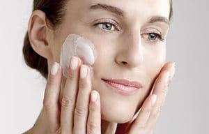 Женщина наносит очищающее молочко на лицо.