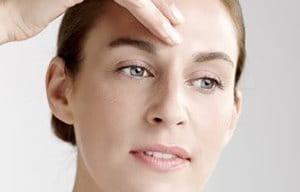 Женщина наносит концентрат на лоб