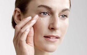 Женщина наносит крем для ухода за кожей вокруг глаз.